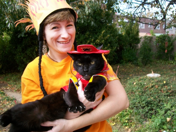 A silly woman wearing a paper printout of fire on her head holds a cat dressed like a fireman.