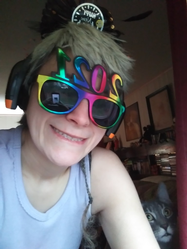 """A photo of Lynda, wearing the 2021 glasses and a ridiculous hairband that reads """"Happy New Year!"""" The kitten sits next to me, looking like he wants to eat the hairband."""